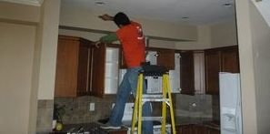 Water Damage Technician Conducting Ceiling Repair